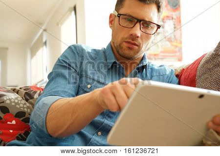 Man with eyeglasses websurfing on digital tablet at home