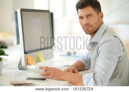 Handsome businessman working on desktop computer in office