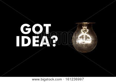 Bulb with message GOT IDEA? on black background