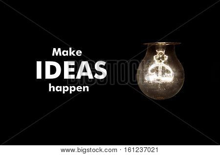 Bulb with message MAKE IDEAS HAPPEN on black background