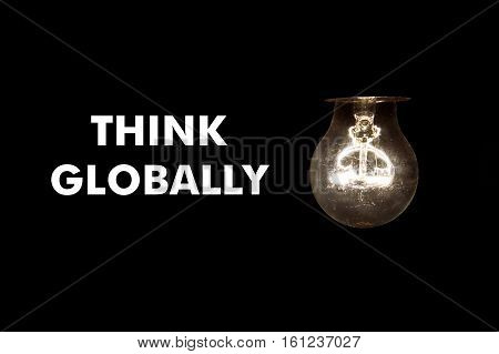 Bulb with message THINK GLOBALLY on black background