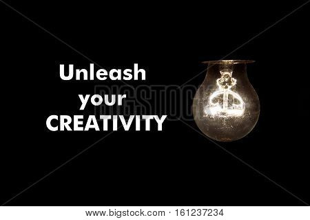 Bulb with message UNLEASH YOUR CREATIVITY on black background