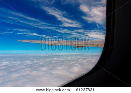 Clouds And Sky  Airplane Wing As Seen Through Window Of An Aircraft