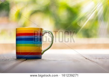 Rainbow cup green inside on wooden background