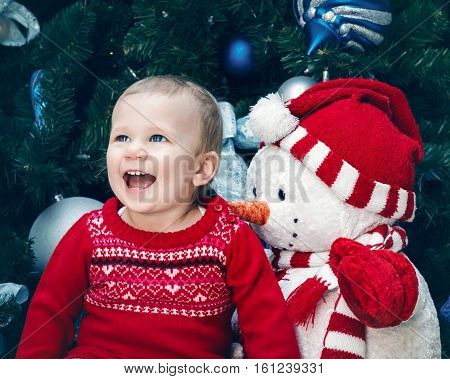 Portrait of happy smiling Caucasian baby girl toddler with blue eyes in red dress sitting by New Year tree near snowman toy emotional authentic lifestyle image.