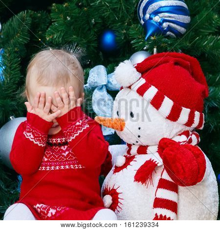 Portrait of little small Caucasian baby girl toddler in red dress sitting by New Year tree with snowman toy closing covering her eyes with hands in surprise childhood happiness