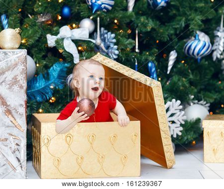 Portrait of happy funny smiling Caucasian baby girl toddler in red holiday dress sitting in large gift present box under New Year tree holding ornaments decoration.
