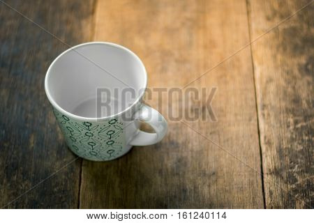 White Cup With Green Pattern On Wooden Background