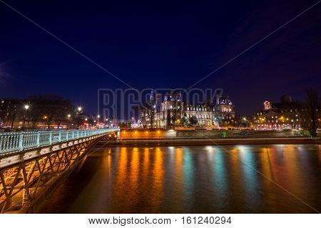 Bridge by the Seine river with view on the Hotel de ville in Paris at night