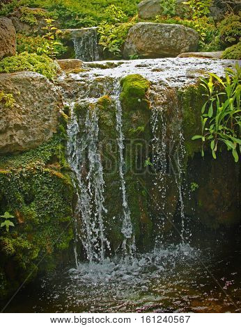 photograph of a small trickling waterfall in a rock garden