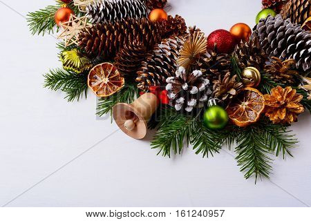 Handmade wooden Christmas jingle bell fir branches and pine cones. Christmas decoration with ornaments and dried orange slices. Christmas greeting background. Copy space.