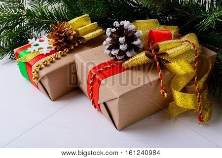 Christmas presents decorated with snowy and golden pine cones. Christmas background with kraft paper wrapping gift boxes.