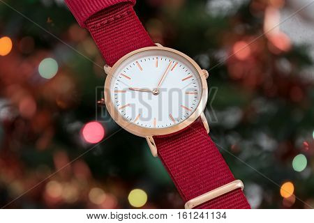 Red nylon strap wrist watch in Christmas time in front of Christmas tree lights background