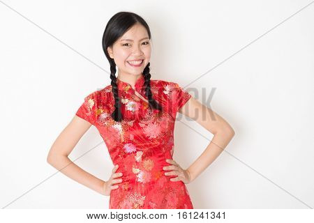 Portrait of young Asian girl in traditional qipao dress smiling, celebrating Chinese Lunar New Year or spring festival, standing on plain background.
