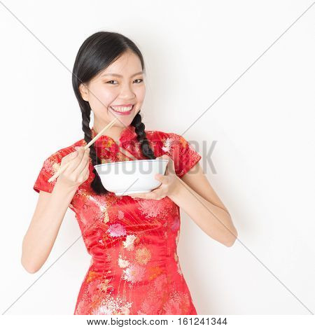 Portrait of young Asian woman in traditional qipao dress eating, hand holding bowl and chopsticks, celebrating Chinese Lunar New Year or spring festival, standing on plain background.
