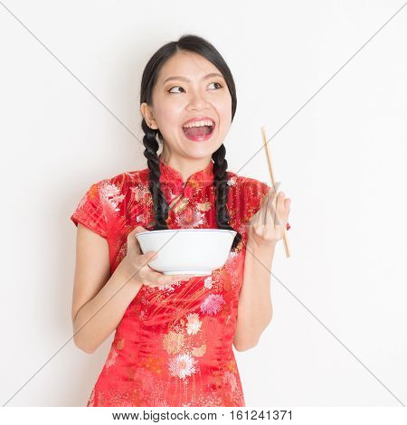 Portrait of young Asian woman in traditional cheongsam dress eating, hand holding bowl and chopsticks, celebrating Chinese Lunar New Year or spring festival, standing on plain background.