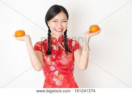 Young Asian woman in traditional qipao dress holding mandarin orange and smiling, celebrating Chinese Lunar New Year or spring festival, standing on plain background.
