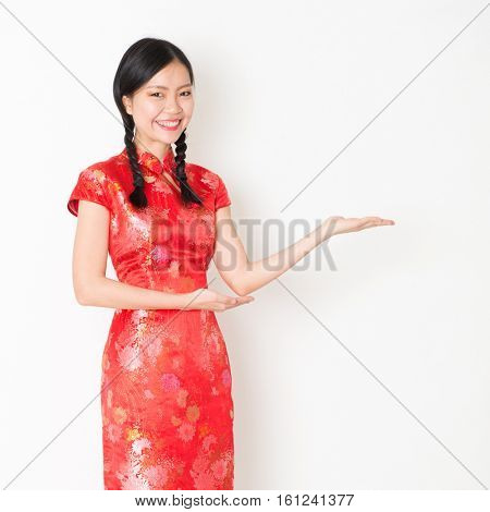 Portrait of young Asian woman in traditional qipao dress smiling and hand showing something, celebrating Chinese Lunar New Year or spring festival, standing on plain background.