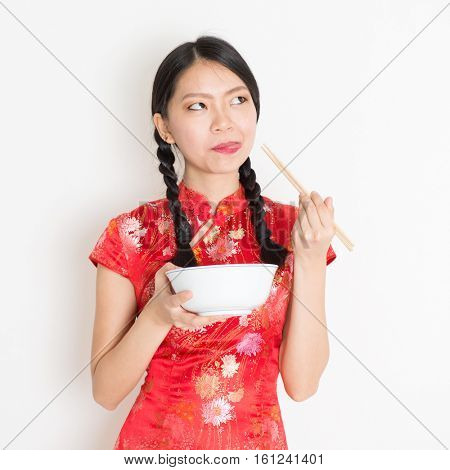 Portrait of young Asian girl in traditional cheongsam dress eating, hand holding bowl and chopsticks, celebrating Chinese Lunar New Year or spring festival, standing on plain background.
