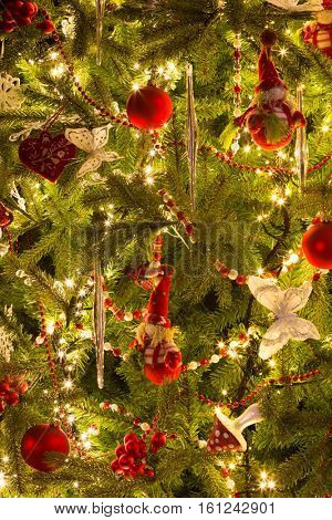 Ornaments like santa puppets and butterflies in a decorated christmas tree