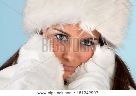 Winter girl with white fur hat wearing warm fur hat