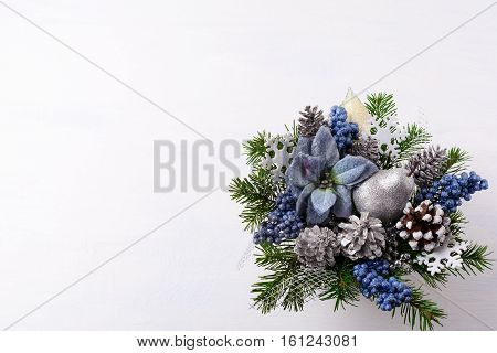 Christmas background with silver glitter decor and blue silk poinsettias. Artificial Christmas flower arrangement with pine cones and fir branches. Christmas table centerpiece. Copy space.