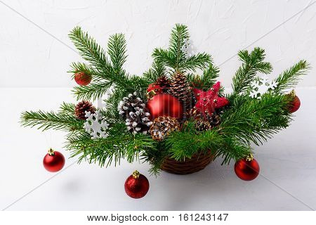 Christmas table centerpiece with red ornaments and rustic straw star. Christmas decoration with fir branches and red baubles. Christmas background with greenery in wicker basket.