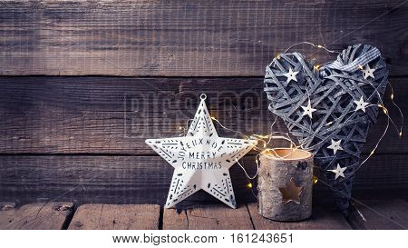 Christmas star decorative heart candleholder and fairy light on aged wooden background. Decorative christmas composition. Place for text. Toned image.