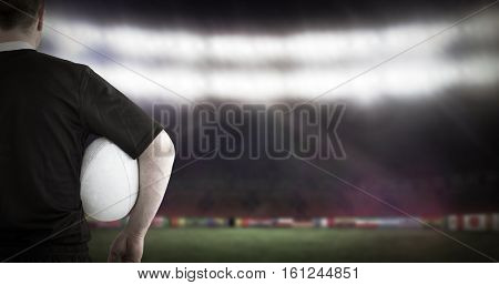 3D Rugby player holding a rugby ball against football pitch with world cup flags