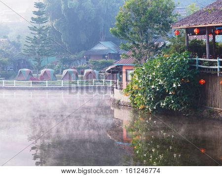 Village and lake landscape view in the morning with mist at Rak Thai Village Mae Hong Son Province Thailand