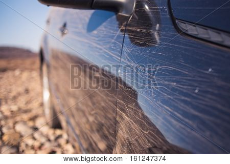 dirty scratches on the surface of a body of black car, selective focus