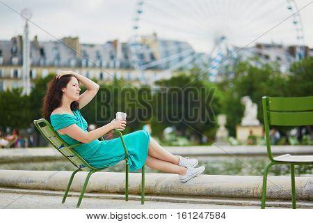 Woman In Green Dress Drinking Coffee In Tuileries Garden Of Paris, France