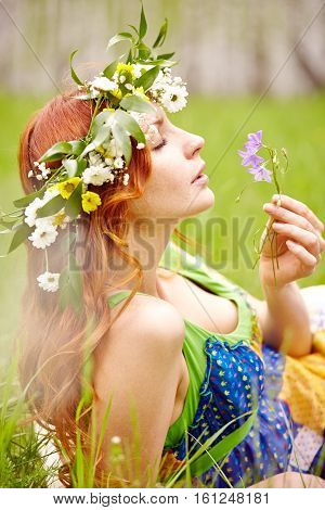 Relaxed woman smelling bluebell lying on grass