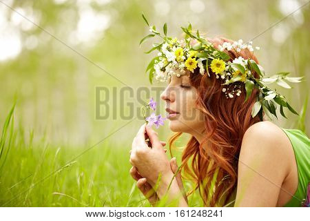 Beautiful woman admiring bluebell flower smell in nature