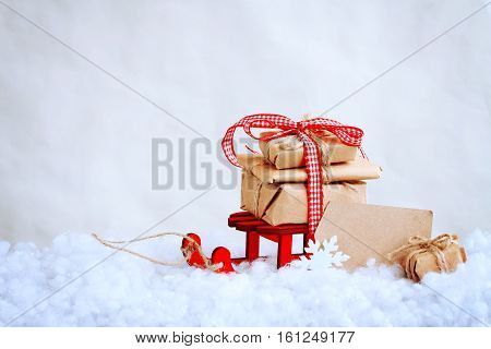 christmas red toy sled with a pile of gifts paper tag retro style background