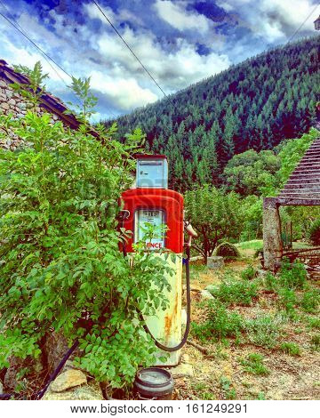 Vintage fuel pump standing in the middle of the mountains in the ardèche in France