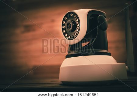 Security camera on Wood table. IP Camera with vintage color effect