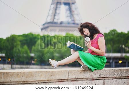 Girl With Coffee To Go Reading A Book Near The Eiffel Tower.