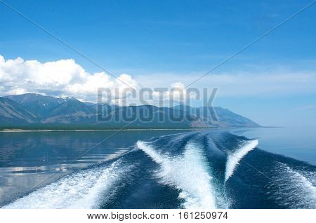 waves from a boat on Lake Baikal with mountain background, Russia