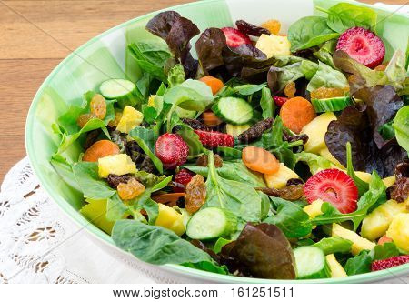 Fresh garden salad close up harvest of fresh lettuce strawberries carrots cucumber and pineapple with raisins
