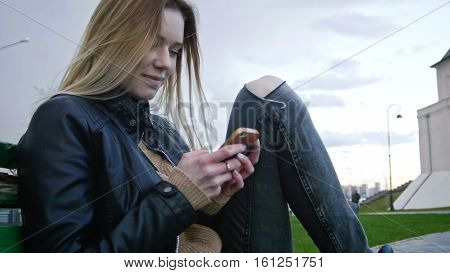 Cute happy girl with long blonde hair in leather jacket straightens hair use gadget sitting on the bench, close-up, horizontal