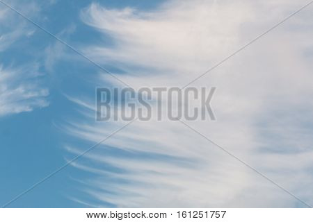 A blue sky with strands of Cirrus clouds.