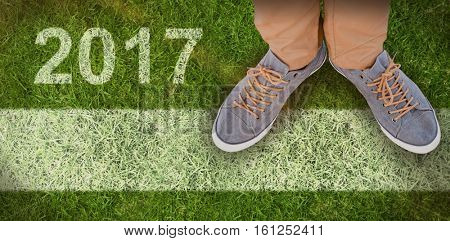 Low section of man wearing shoes against closed up view of grass