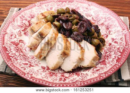 Chicken breasts braised with olives on plate on woden table