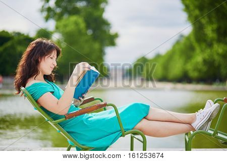 Woman Reading A Book In Tuileries Garden Of Paris, France