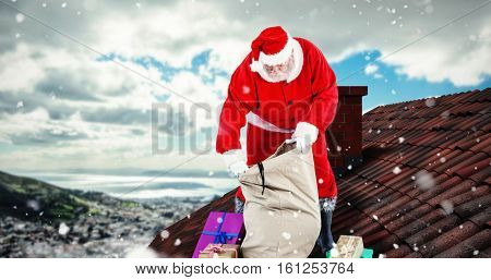 3D Santa Claus filling gift boxes in sack against landscape of city and cloudy sky