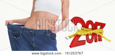 3D Digitally generated image of new year with tape measure against midsection of woman wearing old pants after losing weight and gesturing thumbs up