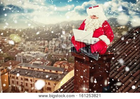 3D Santa sitting and using his laptop against beautiful view over houses