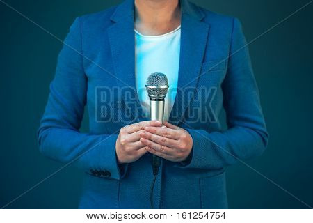 Elegant female television journalist doing business reportage holding microphone in hands breaking news concept