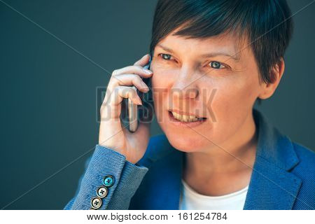 Irritated angry business woman during mobile phone conversation showing her teeth